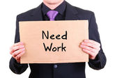 "Unemployed businessman with cardboard sign ""Need Work"" — Stockfoto"