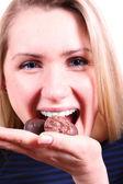 Lachende vrouw eten chocolade snoepjes — Stockfoto