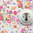 Old light switch on vintage floral wallpaper — Stock Photo