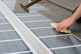Muž instalací laminátové podlahy nad infračervený uhlíku, topný systém — Stock fotografie
