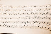 Musical notes in old music book — Stock Photo