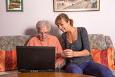An old woman with a laptop — Stock Photo