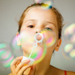 Portrait of funny lovely little girl blowing soap bubbles — Stock Photo #9359652
