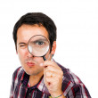Funny young man looking through magnifying glass, isolated on wh — Stock Photo #9359664