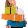 Beautiful young woman with lots of gifts looking up on white bac — Stock Photo