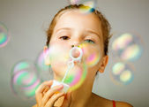 Portrait of funny lovely little girl blowing soap bubbles — Stock Photo