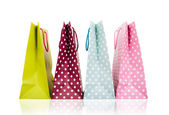 Assorted colored shopping bags on white background — Stock fotografie