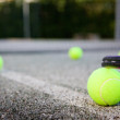 Tennis ball and racket on the court line — Stock Photo