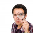 Funny image of a young man looking through magnifying glass, iso — Stock Photo #9360100