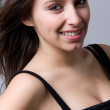 Closeup portrait of a beautiful young woman smiling, against a g — Stock Photo