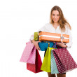 Beautiful young womcarrying shopping bags and gifts on white — Stok Fotoğraf #9361010
