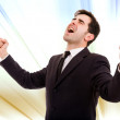 Champion business man standing with fists clenched in victory — Stock Photo