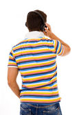 Back view of a young man listening music with headphones, isolat — Stock Photo