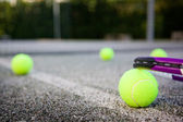 Tennis ball and racket on the court line — Stok fotoğraf