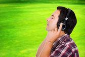 Bel giovane uomo ascoltando musica nel parco — Foto Stock