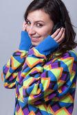 Genç kadın, mavi bir arka plan üzerinde kulaklık ile müzik dinlemek — Stok fotoğraf