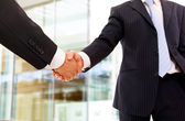 Closeup of business shaking hands at the office — Stock Photo