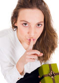 Happy woman holding a gift box and givin hush sign for suprise — Stock Photo