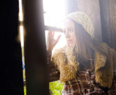 Beautiful young woman looking through window with soft light in — Photo