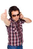 Feliz joven con el pulgar para arriba y escuchar música — Foto de Stock