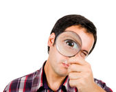Funny image of a young man looking through magnifying glass. ( f — Stock Photo