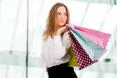 Young beautiful woman with shopping bags on the background of sh — Stock fotografie
