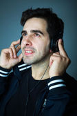 Handsome young man listening the music in headphones — Stock Photo