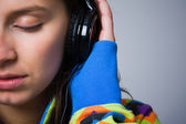 Close-up of a young girl listening to music with headphones — Stock Photo