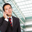 A handsome business man talking on the phone at his office build — Stock Photo