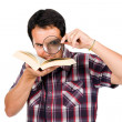 Young man reading a interesting book with magnifying glass, isol — Stock Photo