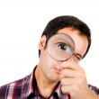 Young man looking through magnifying glass — Stock Photo #9379216