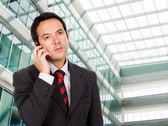 Krásný obchodní muž mluví po telefonu v jeho kanceláři sestavení — Stock fotografie