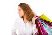 Beautiful young woman carrying shooping bags on white background — Stok fotoğraf