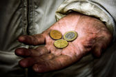 A beggar with some coins on his dirty hands — Stock Photo