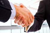 Closeup of business shaking hands over a deal — Stock Photo