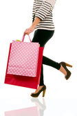 Waist-down view of woman carrying shopping bags — Stockfoto