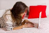 Junge schöne frau auf dem bett liegend mit laptop — Stockfoto