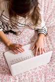 Young woman lying on the bed with laptop — Stock Photo