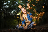 Beautiful young girl with falling leaves — Stock Photo