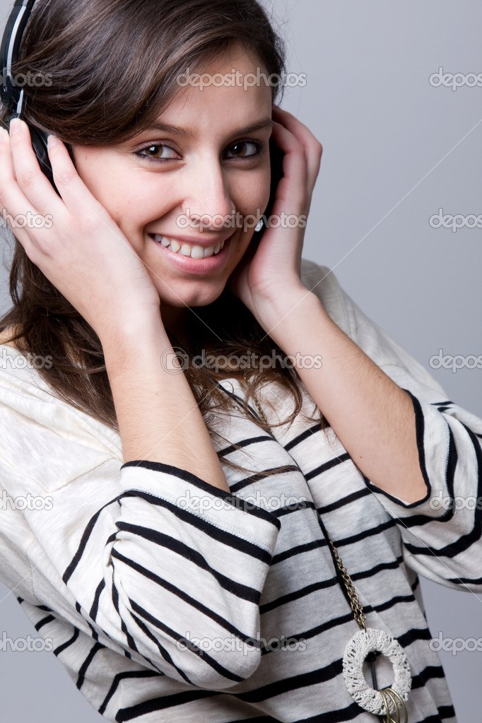 Smiling young woman listening to music over grey background — Stock Photo #9378954
