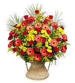 Basket of roses, gerberas and palm leaves — Stock Photo
