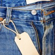 Stock Photo: Unbuttoned blue jeans with paper label