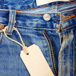 Unbuttoned blue jeans with paper label — Stock Photo #9544830