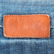 Blank leather jeans label sewed on blue jeans - Stock Photo