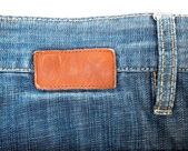 Blank leather label sewed on blue jeans — Stock Photo