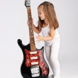 Small child hold red acoustic guitar. Music concept. On gray bac — Stock Photo #8397551