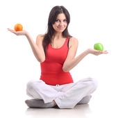Young woman in a pose of a lotus, with apple and orange. Isolate — Stock Photo