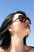Woman with sunglasses smelling the fresh air — Stock Photo