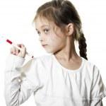 Little girl shows ballpoint pen — Stock Photo