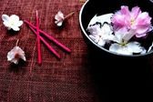 Black bowl of cherry blossom with incense — Stock Photo